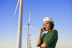 A female engineer against a background of wind turbines.